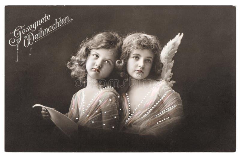 O branco das meninas do anjo voa o cartão de cumprimentos do Natal foto de stock