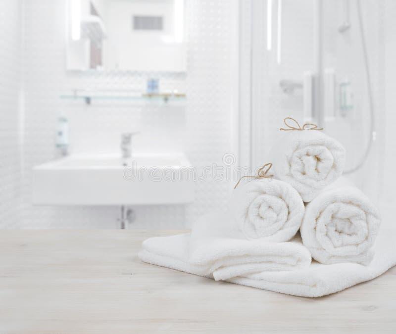 O branco dobrou toalhas dos termas em fundo interior defocused do banheiro fotos de stock royalty free