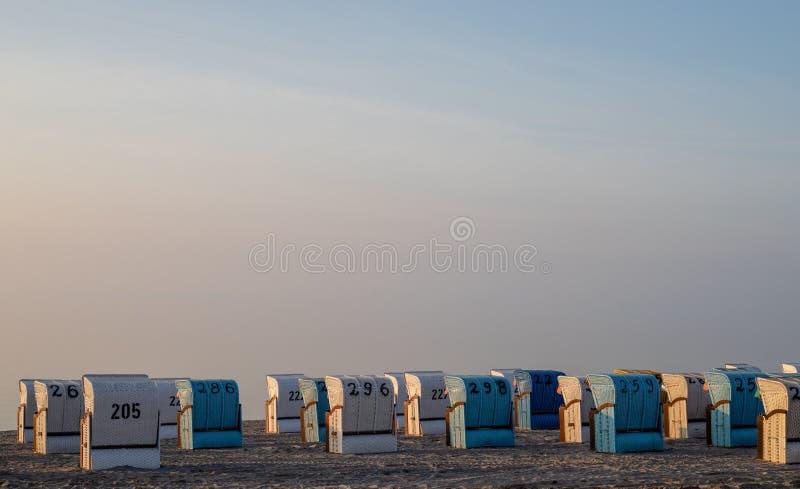 O branco e o azul coloridos telharam a cadeira de praia na praia do mar Báltico dentro imagem de stock