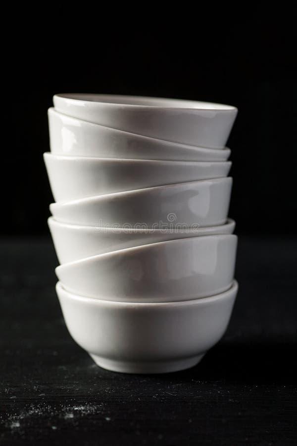 O branco empilhou bacias cerâmicas em uma tabela de madeira preta, vertical fotos de stock royalty free
