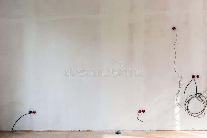 O branco emplastrou as paredes que se prepararam à pintura com o bonde não instalado e cabos ethernet e tomadas dentro imagem de stock