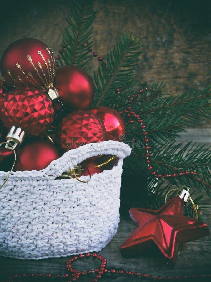 O branco faz crochê em volta da cesta com as decorações vermelhas do Natal no fundo de madeira Fundo do cartão do ano novo e do X fotografia de stock royalty free