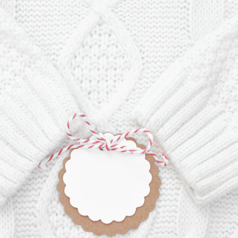 O branco festivo fez malha a camiseta do inverno com uma etiqueta para felicitações Feriados de inverno quadrado foto de stock royalty free