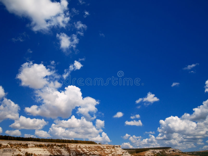 O branco nubla-se o sol do céu azul fotografia de stock