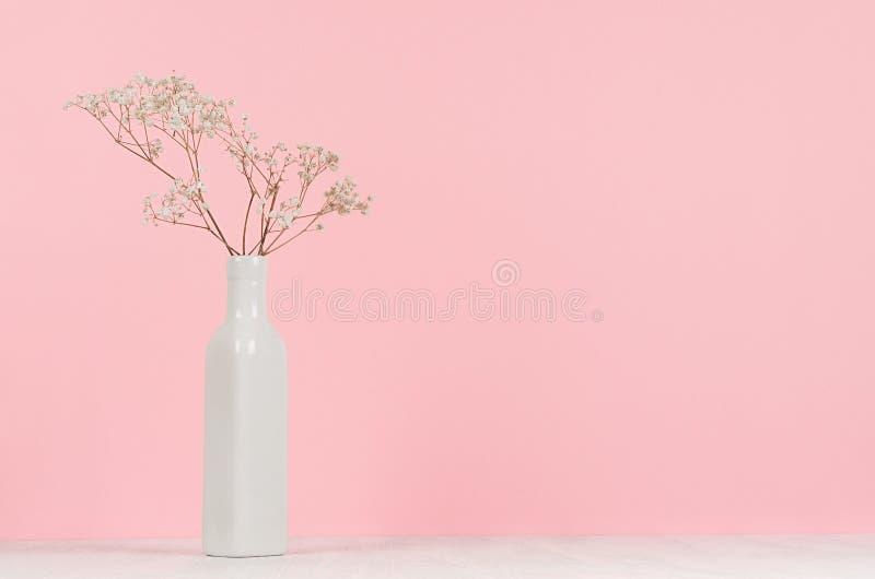 O branco pequeno secou flores no vaso cerâmico alto elegante no fundo macio do rosa pastel, espaço da cópia imagens de stock royalty free