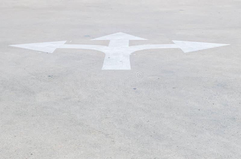 O branco velho do close up e pálido de superfície pintou o sinal da seta no fundo textured assoalho da rua do cimento com espaço  fotografia de stock