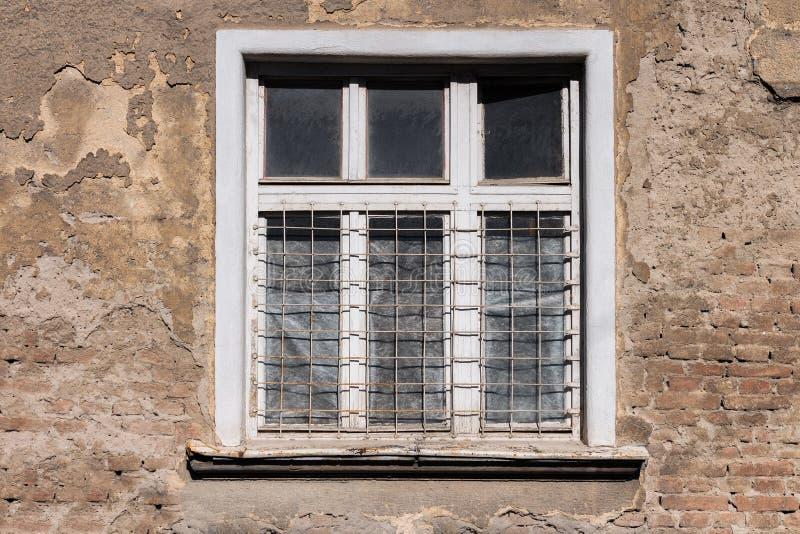 O branco velho moldou a janela em uma construção velha, arruinada fotografia de stock royalty free