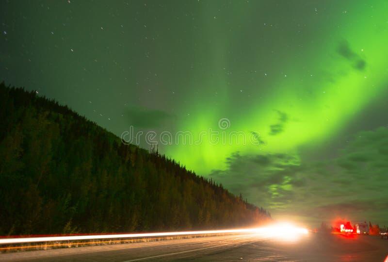 O brilho da aurora boreal como a tração dos viajantes sobre a olhar ACIMA fotos de stock