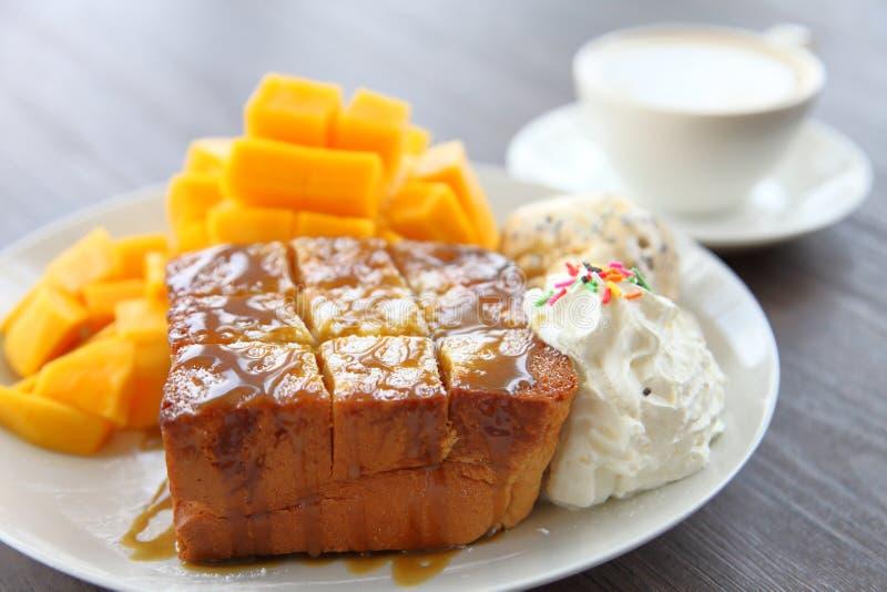 O brinde do mel serviu como a sobremesa com a manga fresca decorativa descascada com café do latte na tabela de madeira marrom es fotos de stock
