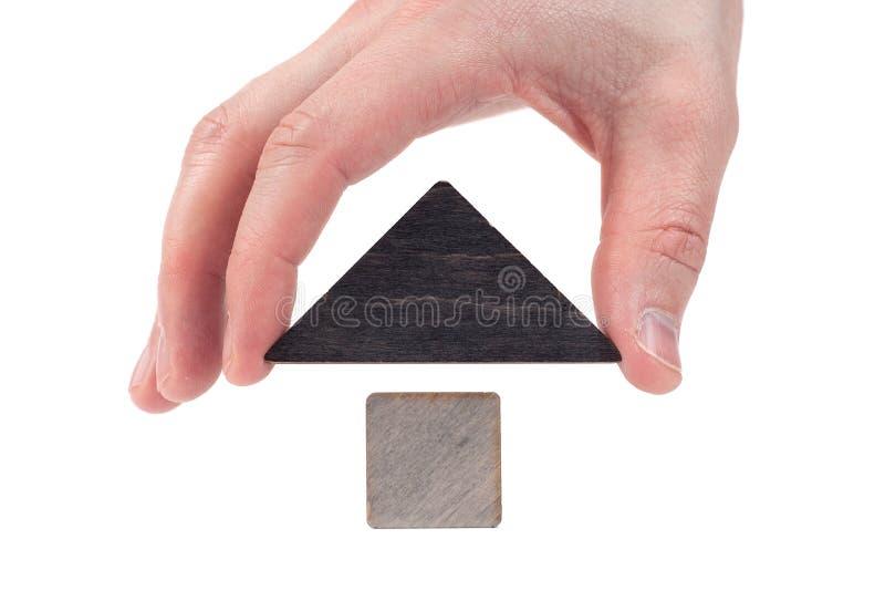 O brinquedo de madeira da casa obstrui o fundo branco isolado, pouca casa de madeira com m?o O conceito de comprar e de vender be fotografia de stock