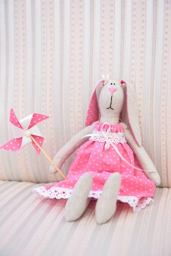 O brinquedo de menina bonito de um coelho no branco pontilhou o vestido fotos de stock royalty free