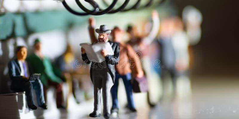 O brinquedo diminuto de um homem no smoking leu o curso do jornal e dos povos do trabalho imagens de stock