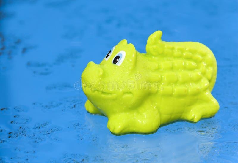 O brinquedo verde do crocodilo está no fundo azul molhado imagens de stock
