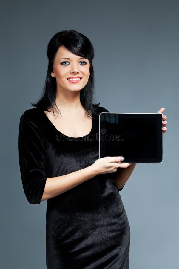 O brunette de sorriso 'sexy' apresenta a almofada de toque nova devic imagens de stock