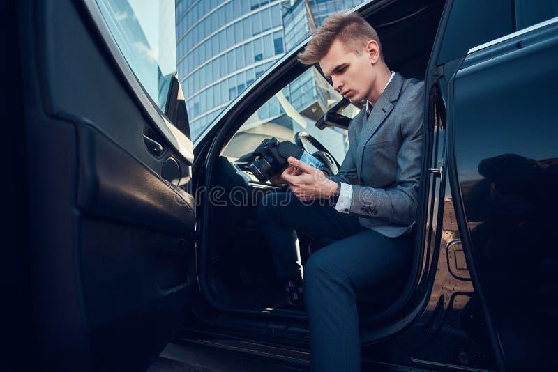 O buisnisman novo est? olhando a seu telefone celular ao sentar-se no carro foto de stock royalty free