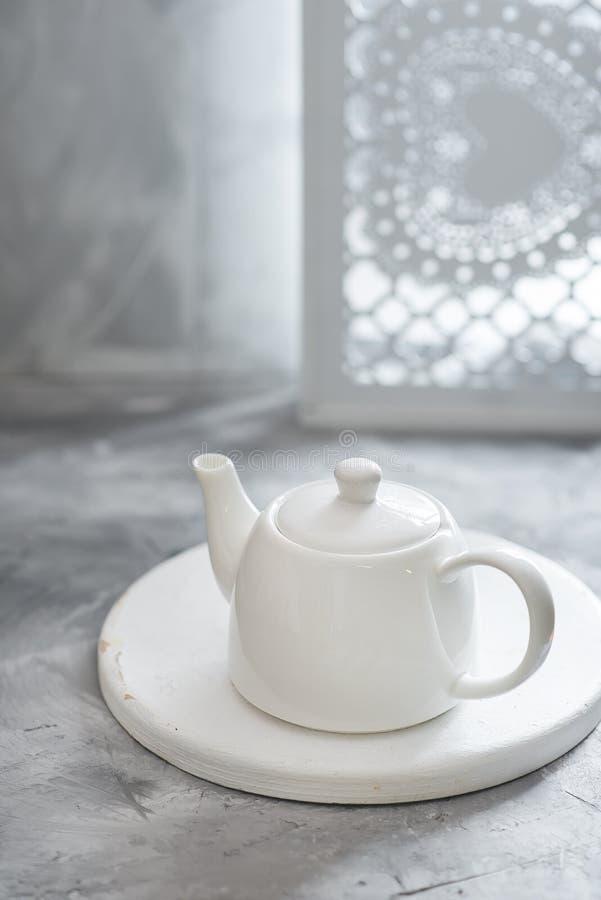 O bule limpo branco da porcelana está no fundo cinzento fotografia de stock