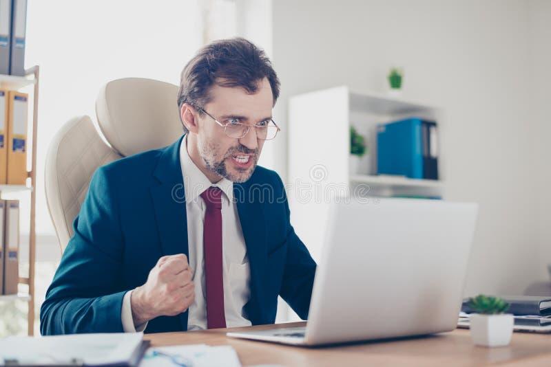 O businessmsn irritado frustrante está gritando em seu portátil no trabalho foto de stock royalty free