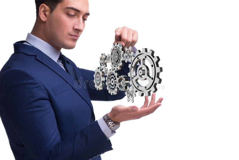 O businessnman no conceito dos trabalhos de equipa com rodas denteadas imagens de stock royalty free