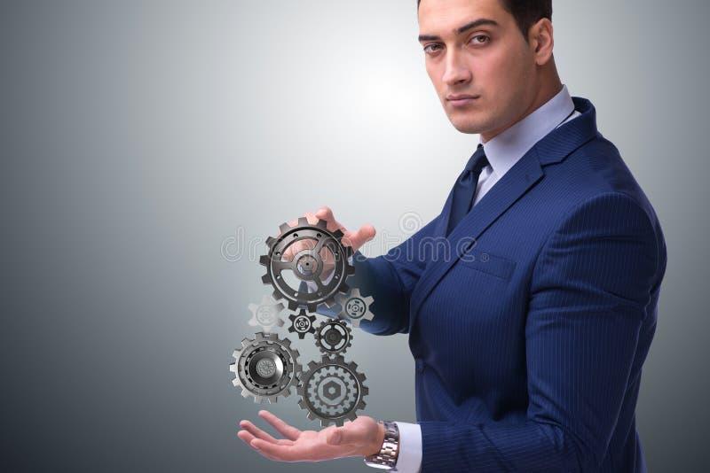 O businessnman no conceito dos trabalhos de equipa com rodas denteadas fotografia de stock