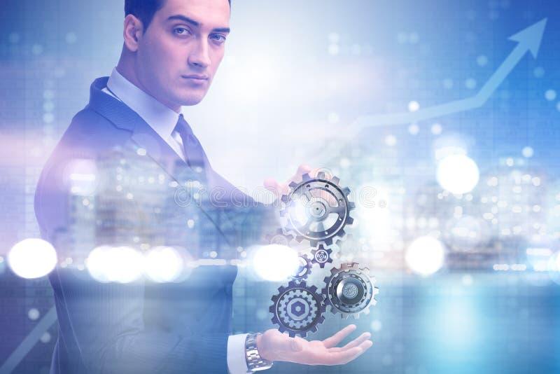 O businessnman no conceito dos trabalhos de equipa com rodas denteadas imagens de stock