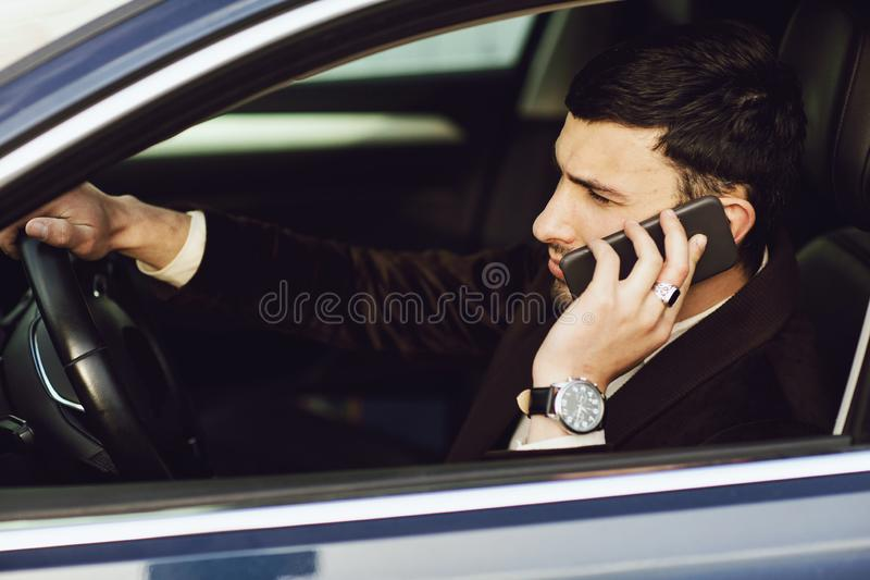 O bussinesman novo no terno fala pelo telefone em seu carro Olhar do neg?cio Movimenta??o do teste do carro novo imagens de stock royalty free