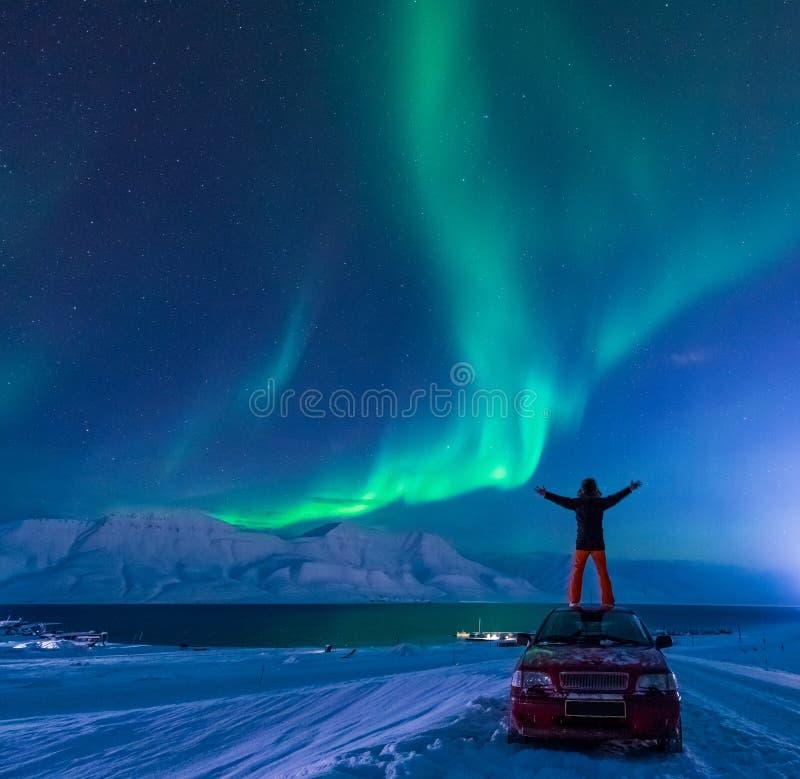 O céu ártico polar do aurora borealis da aurora boreal do homem protagoniza em Noruega Svalbard em montanhas da lua da cidade de  fotografia de stock