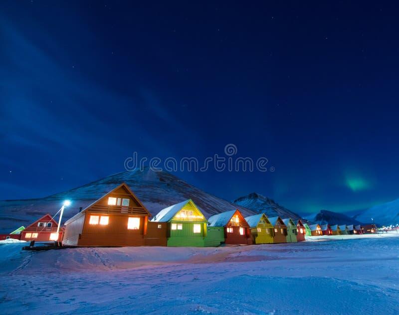 O céu ártico polar do aurora borealis da aurora boreal do homem protagoniza em Noruega Svalbard em montanhas da lua da cidade de  imagem de stock