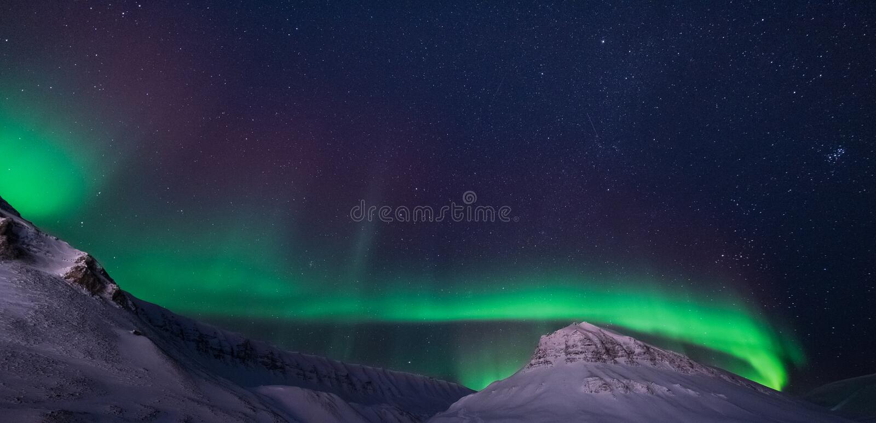 O céu ártico polar do aurora borealis da aurora boreal protagoniza em montanhas do snowscooter da cidade de Noruega Svalbard Long imagem de stock royalty free