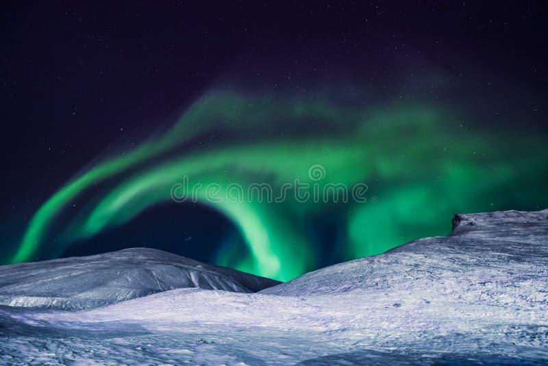O céu ártico polar do aurora borealis da aurora boreal protagoniza em Noruega Svalbard em montanhas da lua da cidade de Longyearb fotografia de stock royalty free