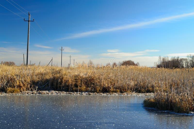 O céu azul claro refletiu em uma lagoa congelada pequena No lado da lagoa é uma linha elétrica fotografia de stock