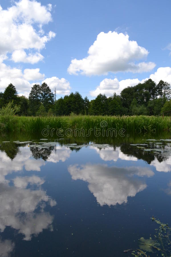 O céu azul e as nuvens brancas refletiram no rio imagem de stock royalty free