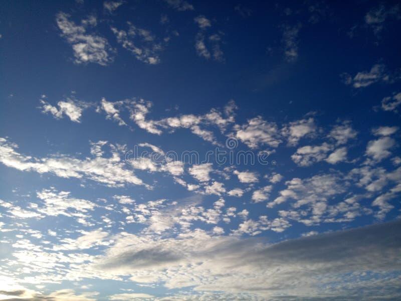 O céu azul e as nuvens douradas no bonito fotografia de stock