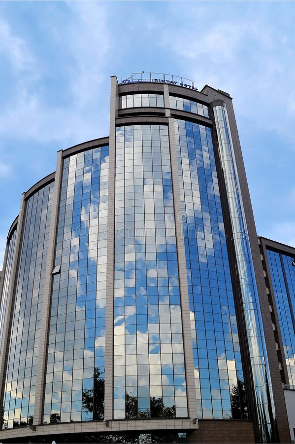 O céu azul e as nuvens são refletidos nas janelas do espelho de um hotel moderno do vidro e do dia concreto, ensolarado, vista da fotografia de stock