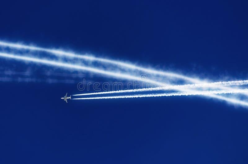 O céu azul e muitos traços do avião do contrail da inversão foto de stock
