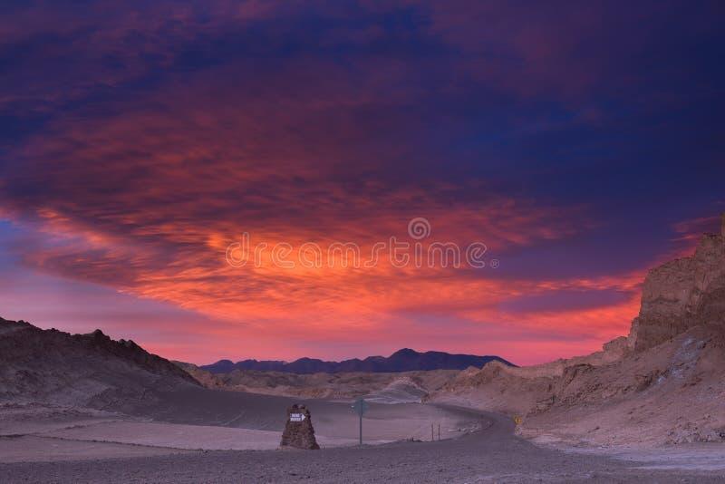O céu brilha belamente durante o por do sol sobre uma estrada no vale da lua, deserto de Atacama, o Chile foto de stock royalty free