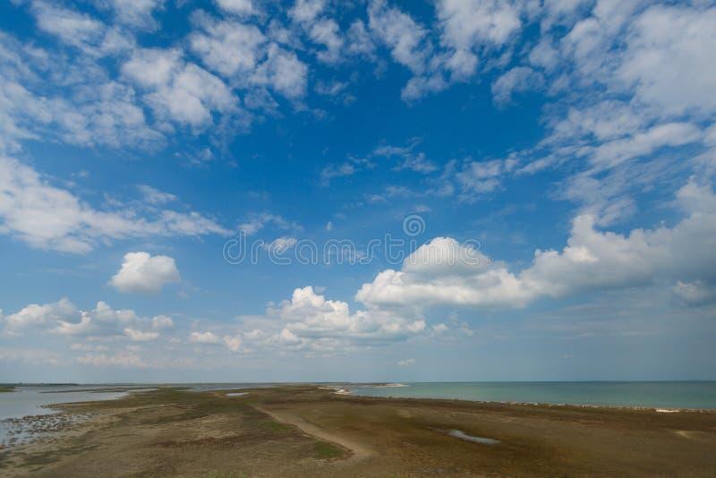 O céu e as nuvens grandes sobre o delta com horizonte alinham imagem de stock