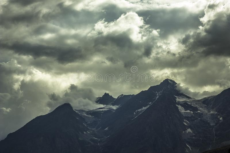 O céu escuro antes de uma tempestade nas montanhas com uma geleira fotografia de stock