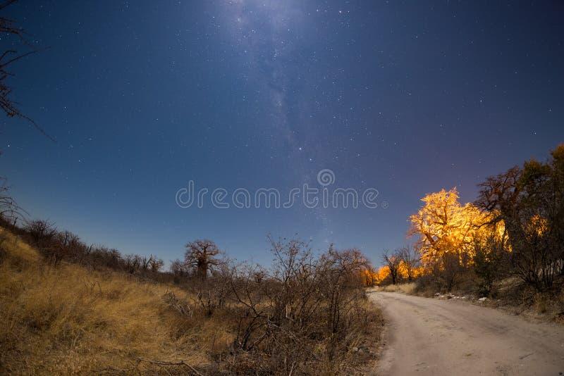 O céu estrelado, o arco da Via Látea e a lua, capturaram do deserto de Kalahari em Botswana, África Luar iluminando a paisagem imagens de stock royalty free