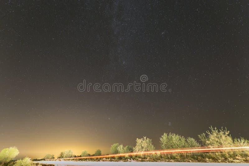 O céu noturno com lote de estrelas brilhantes com árvores e luz do carro arrasta foto de stock