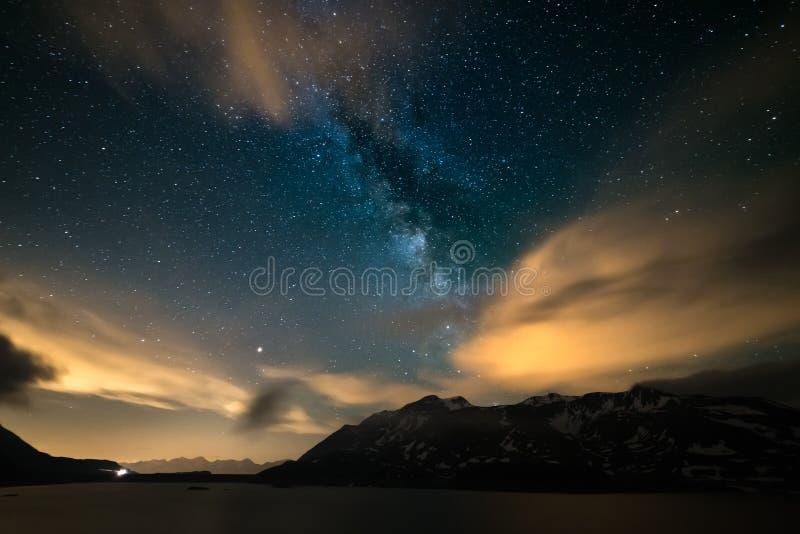 O céu noturno de Astro, galáxia da Via Látea stars sobre os cumes, o céu tormentoso, as nuvens do movimento, a cordilheira snowca imagem de stock royalty free