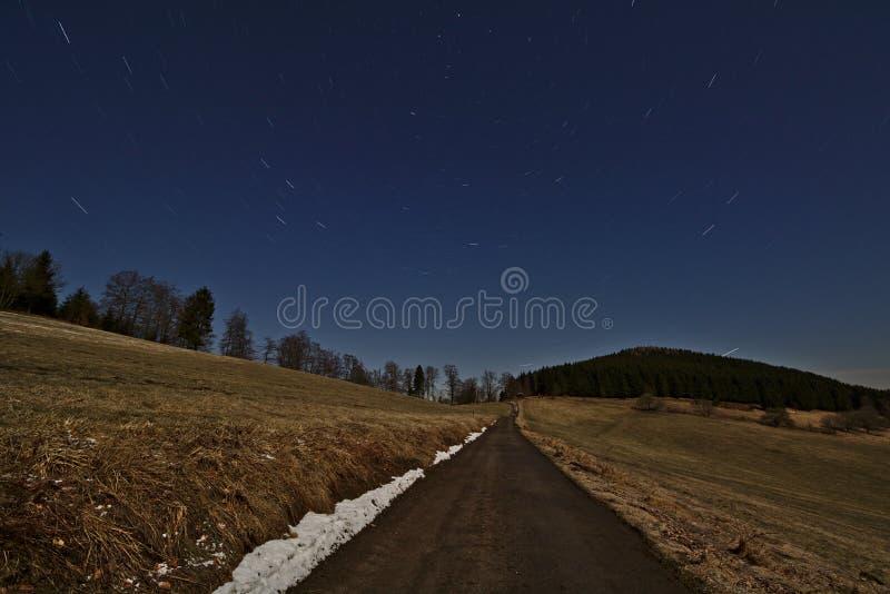 O céu noturno estrelado com estrela arrasta o giro em torno da estrela norte acima de uma única estrada da pista que conduz atrav fotografia de stock