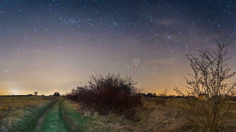 O céu noturno stars com Via Látea sobre o trajeto através dos campos fotografia de stock