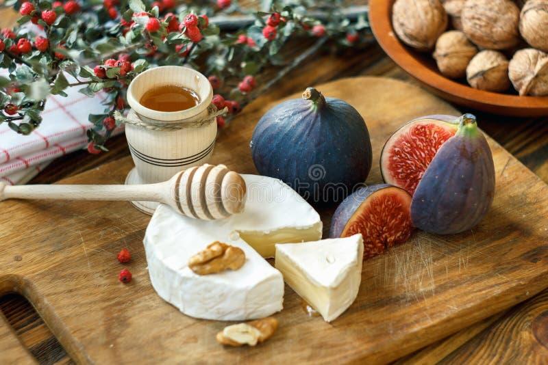O círculo cortado do queijo francês cremoso maduro macio do camembert serviu com os figos, mel e as nozes vermelhos maduros sucul foto de stock royalty free