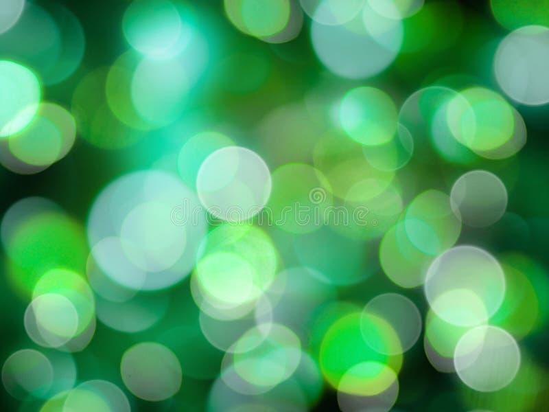 O círculo de incandescência verde-claro e branco borrou luzes em um sumário preto do fundo imagens de stock