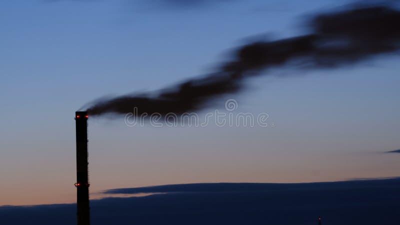 O c?rrego preto do fumo que polui a atmosfera e ? prejudicial ao ambiente sai do calor e da tubula??o do central el?trica foto de stock