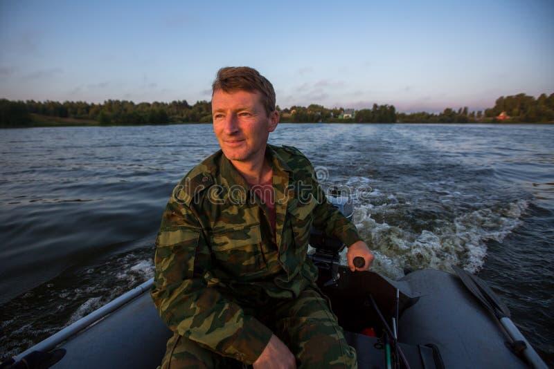 O caçador na camuflagem conduz um barco de motor no lago passatempo fotografia de stock royalty free