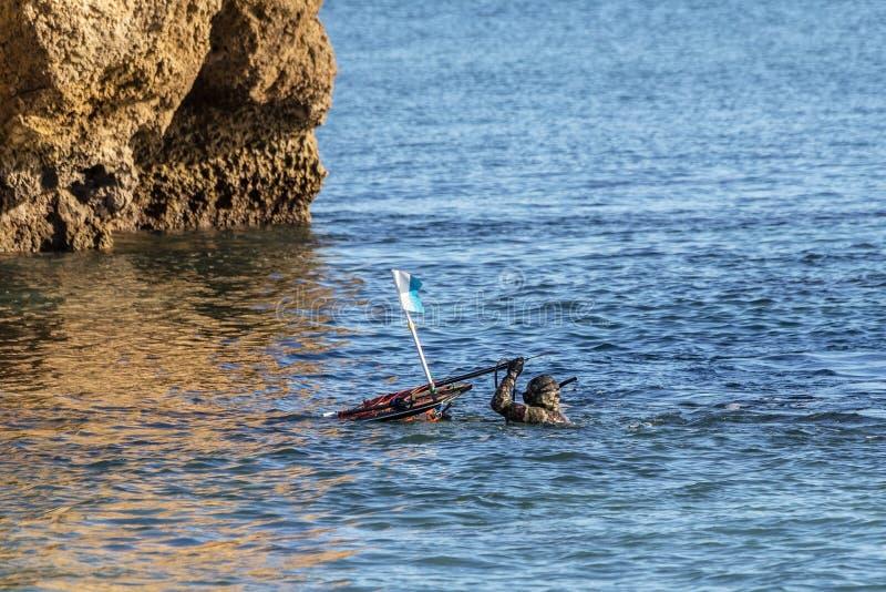 O caçador subaquático, na superfície, ajusta a boia com arpões e bestas foto de stock royalty free