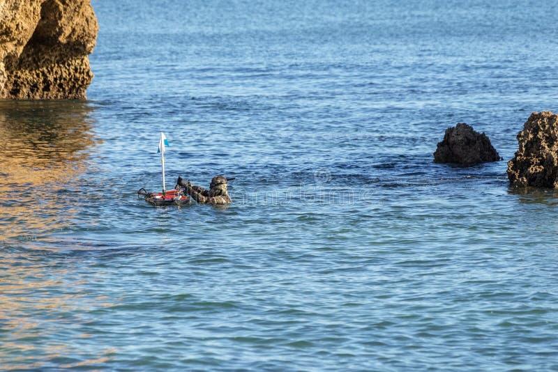 O caçador subaquático, na superfície, ajusta a boia com arpões e bestas imagem de stock royalty free