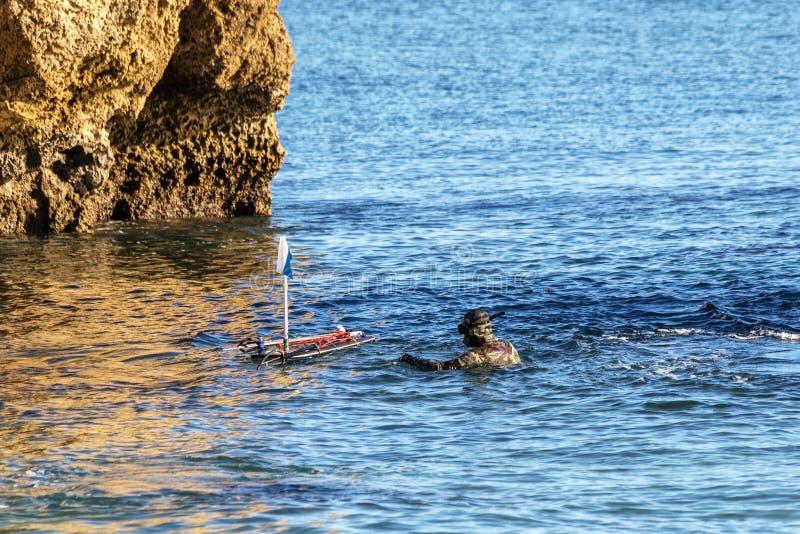 O caçador subaquático, na superfície, ajusta a boia com arpões e bestas fotos de stock