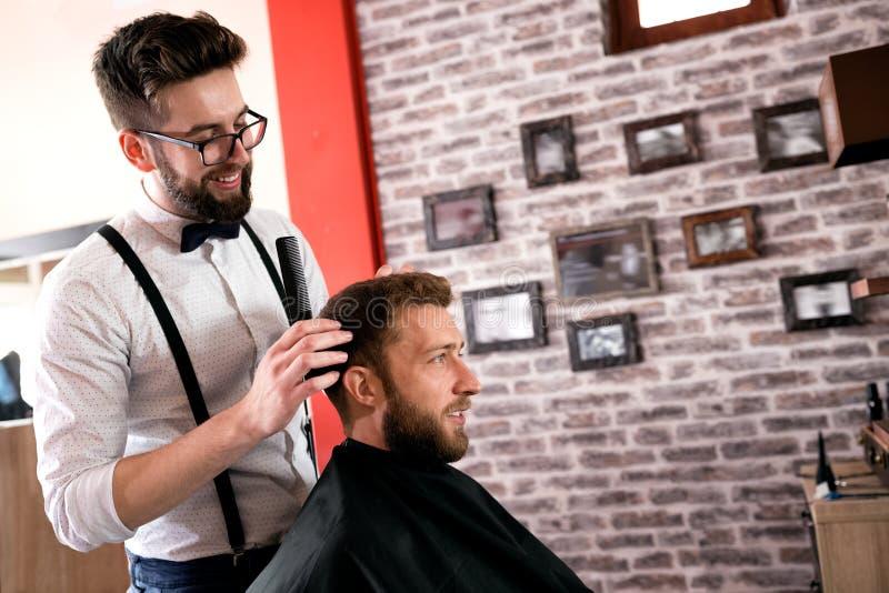 O cabeleireiro ajusta o cabelo um cliente com um pente imagem de stock